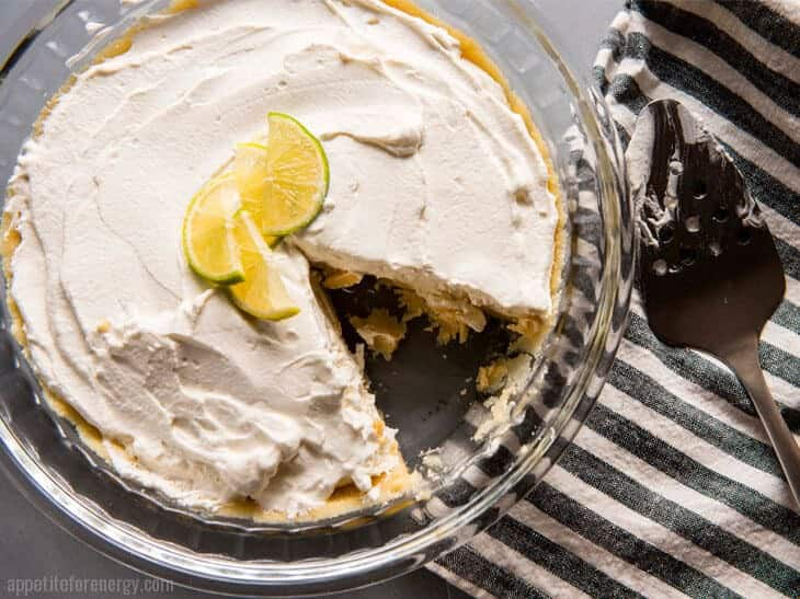 Key Lime Pie Icebox cake in glass dish with a slice removed from pie