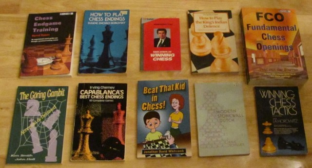 ten chess books on a wooden table