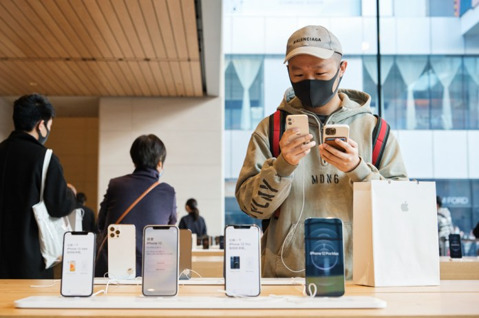Un cliente di Apple Sanlitun esamina da vicino un iPhone 12 mini.