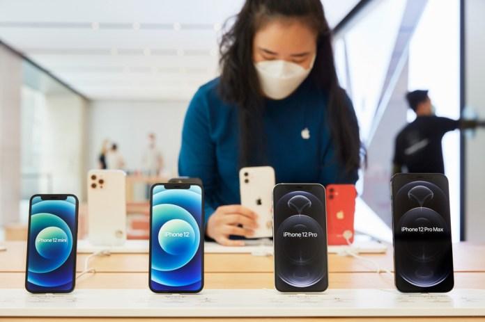 Una dipendente di Apple Sydney sistema un espositore con iPhone 12 mini, iPhone 12, iPhone 12 Pro e iPhone 12 Pro Max.