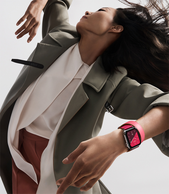 A woman wearing the new Apple Watch Hermès, in a bright color-blocked band.