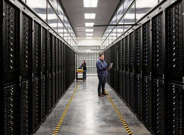 Dois funcionários em sala de servidores de centro de dados da Apple.