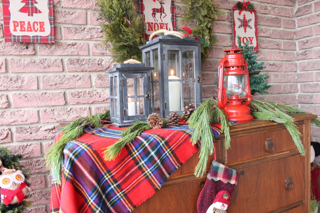 Christmas Front Porch all decked out for the holidays using an plaid scarf, some lanterns and an antique dresser. See all the details at apurdylittlehouse.com