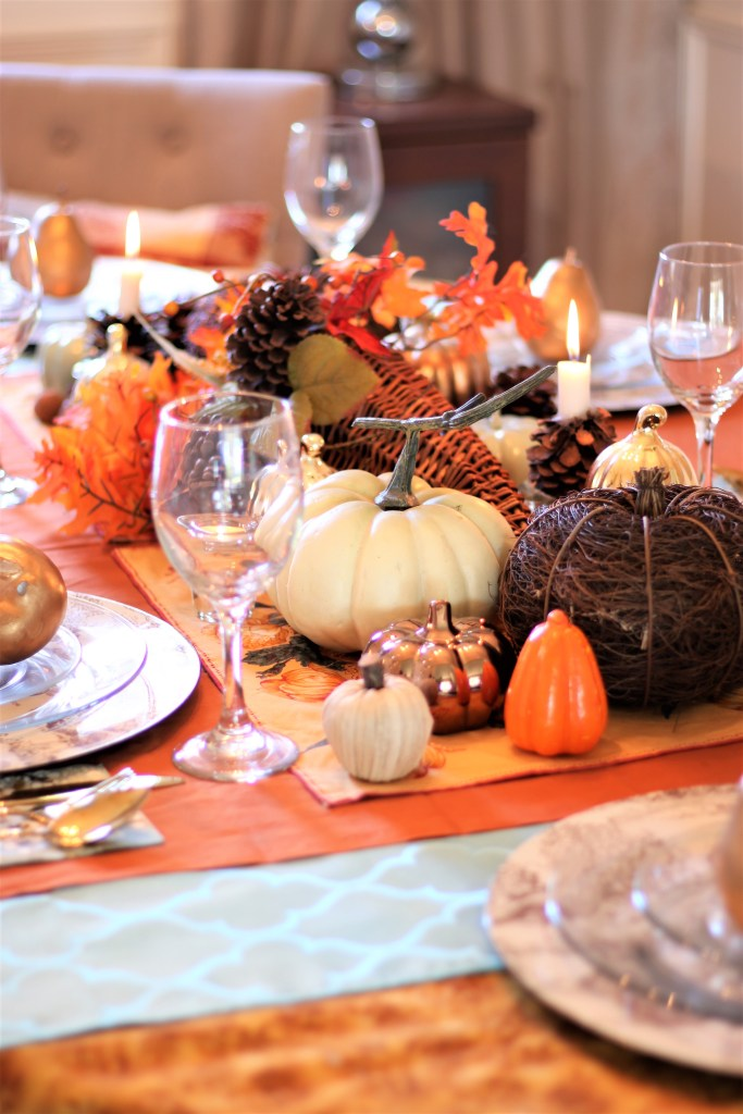 Fall Tablescape against a neutral backgdrop with a cornucopia of colours and textures