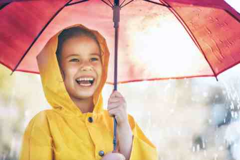 Smiling child in a yellow raincoat holding a red umbrella.
