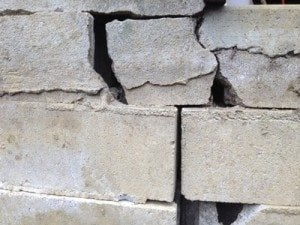 A cement foundation that has bricks cracking