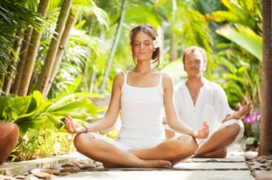 Beautiful couple meditating in the tropical surroundings