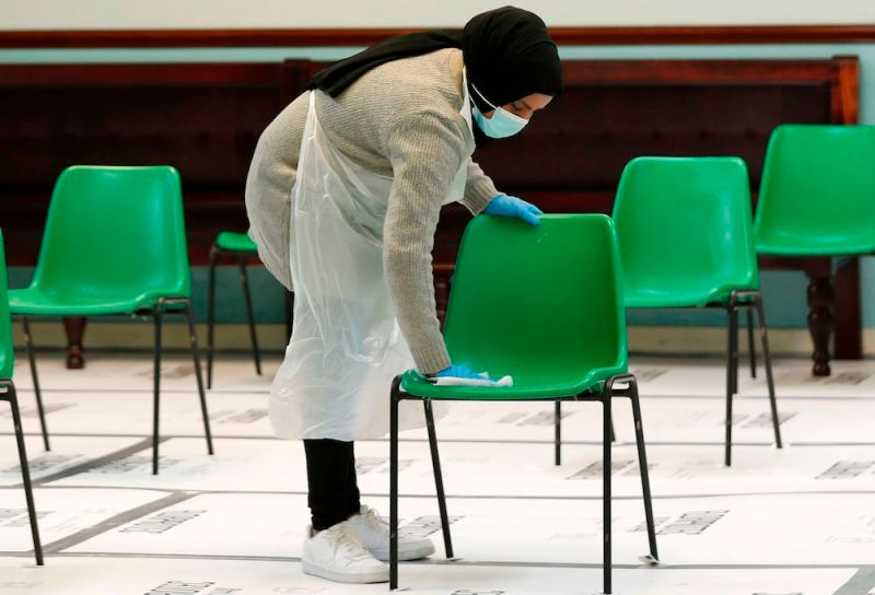 A worker cleans chairs in the waiting area for people receiving the Oxford/AstraZeneca Covid-19 vaccine at the Al-Abbas Islamic Centre, which has been converted into a temporary vaccination centre in Birmingham, central England on January 21, 2021. (AFP)