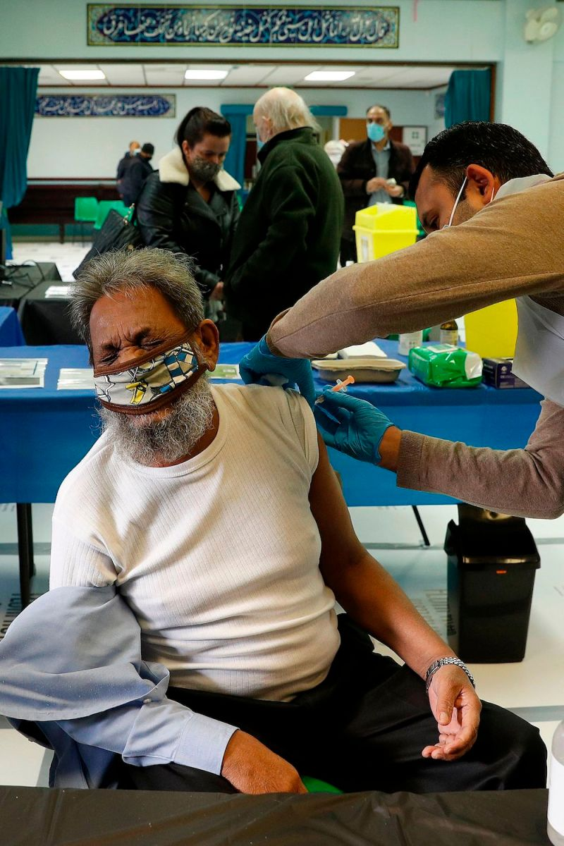 A man grimaces as he receives the Oxford/AstraZeneca Covid-19 vaccine at the Al-Abbas Islamic Centre, which has been converted into a temporary vaccination centre in Birmingham, central England on January 21, 2021. (AFP)