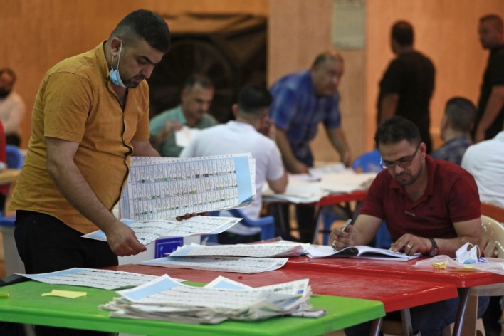 Employees of Iraq's Independent High Electoral Commission conduct a manual count of votes following the parliamentary elections in Baghdad's Green Zone area on Oct. 13, 2021. (AFP)