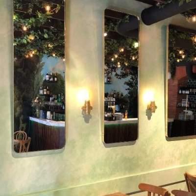 Agencement de la salle de restaurant avec de longs miroirs en laiton polis.