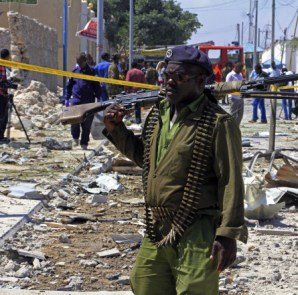A Somali soldier patrols the area of a suicide car bomb attack in Mogadishu, Somalia last month. AP
