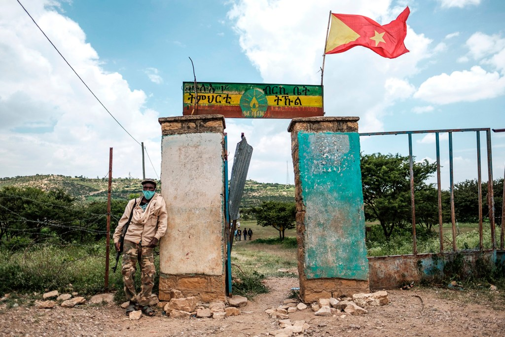 Left: An armed member of the community security force stands in front of a school where a polling station is located during Tigray's regional elections, in Tikul, Ethiopia, on Sept. 9. EDUARDO SOTERAS/AFP via Getty Images Right: Ethiopians, who fled their homes due to ongoing fighting, are pictured at a refugee camp in the Hamdait border area of Sudan's eastern Kassala state on Nov. 12. AFP via Getty Images