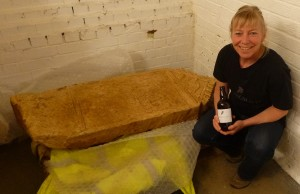 Lucy poses with Bodicacia's tombstone, and a bottle of the ale named in her honour.
