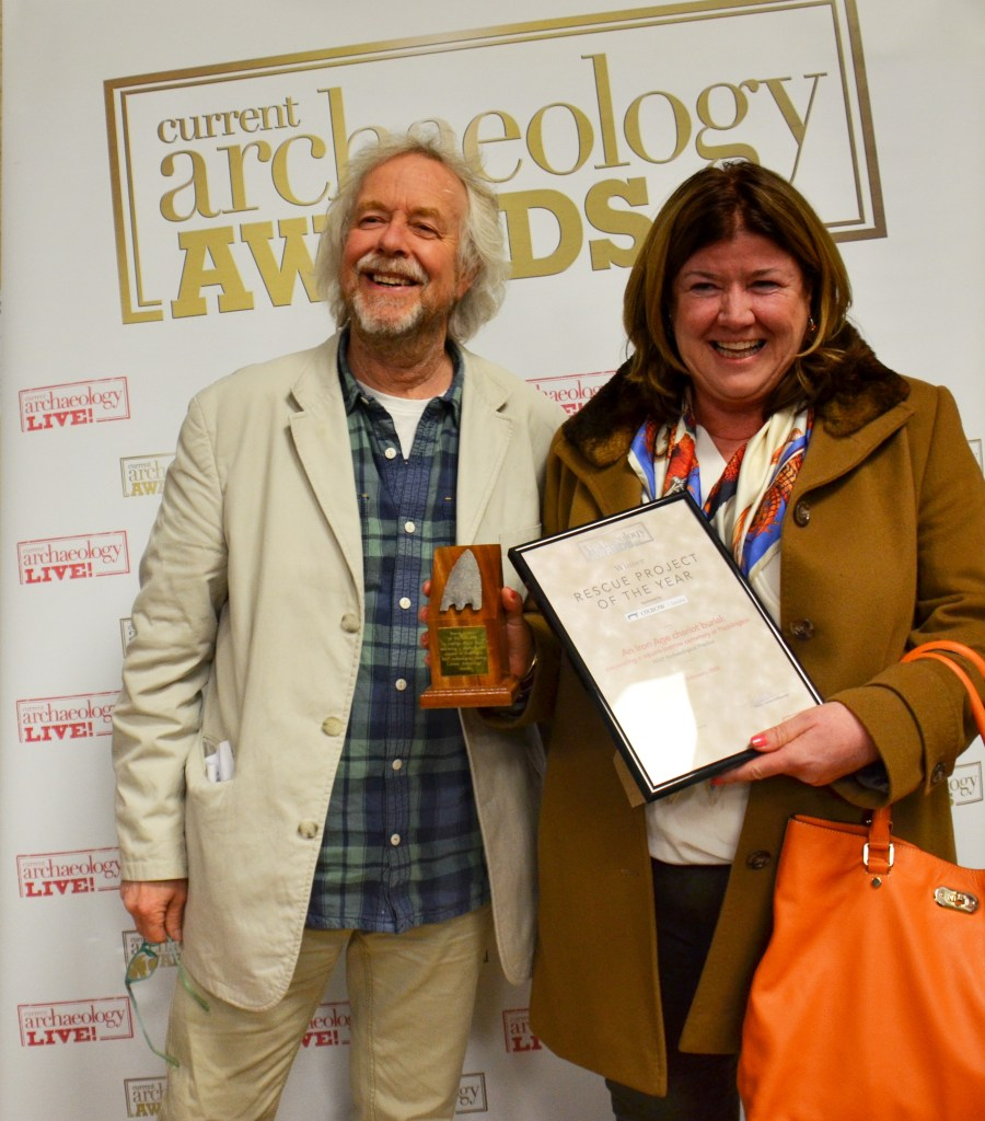 Paula Ware of MAP Archaeological Practice holding the Rescue Project of the Year 2018 award, with the award presenter Julian Richards [Photo Credit: Current Archaeology]