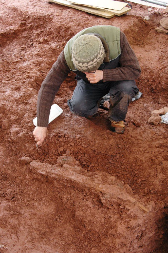 An archaeologist excavating an iron sword, which was also recovered during the dig. [Photo credit: Amgueddfa Cymru – National Museum Wales]
