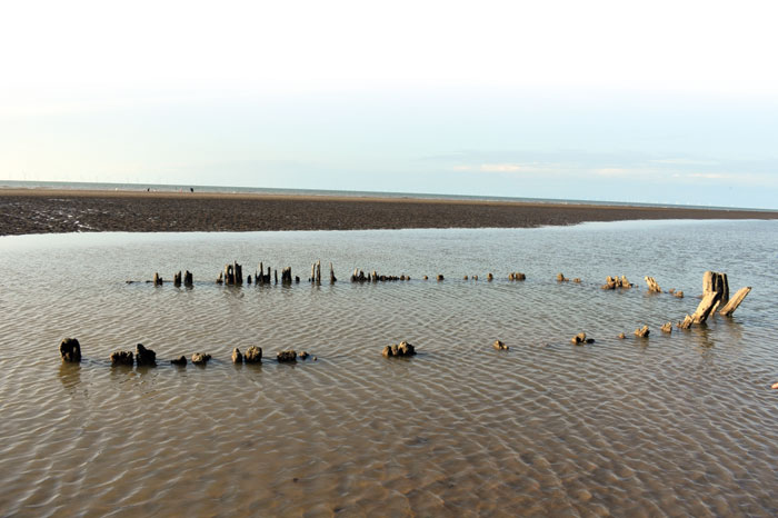 The remains of a wooden ship were identified near a tidal pond in Abergele after summer storms uncovered the wreck. It had been buried for over a century.