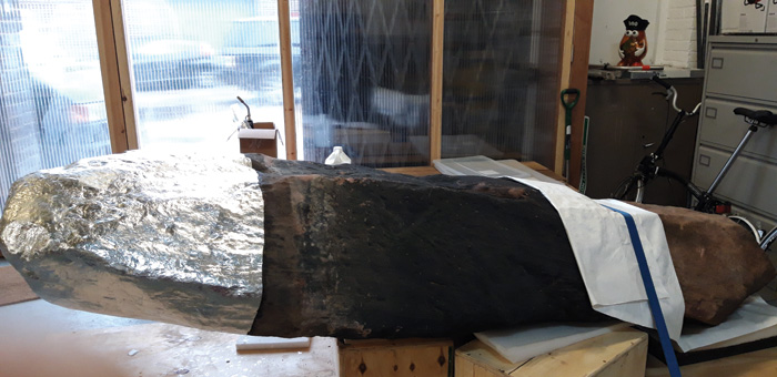The lower end of this stone has been wrapped in aluminium foil, a protective barrier layer that has been applied as part of the remounting process before the stones are reinstalled.