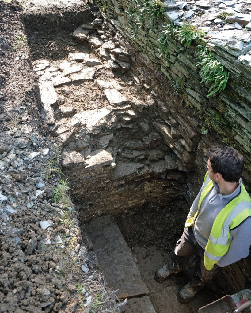 An archaeologist assessing the steps found behind the kitchen garden wall