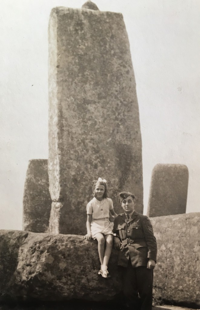 A young girl sat on one of the stones at Stonehenge, with a man in RAF uniform stood next to her