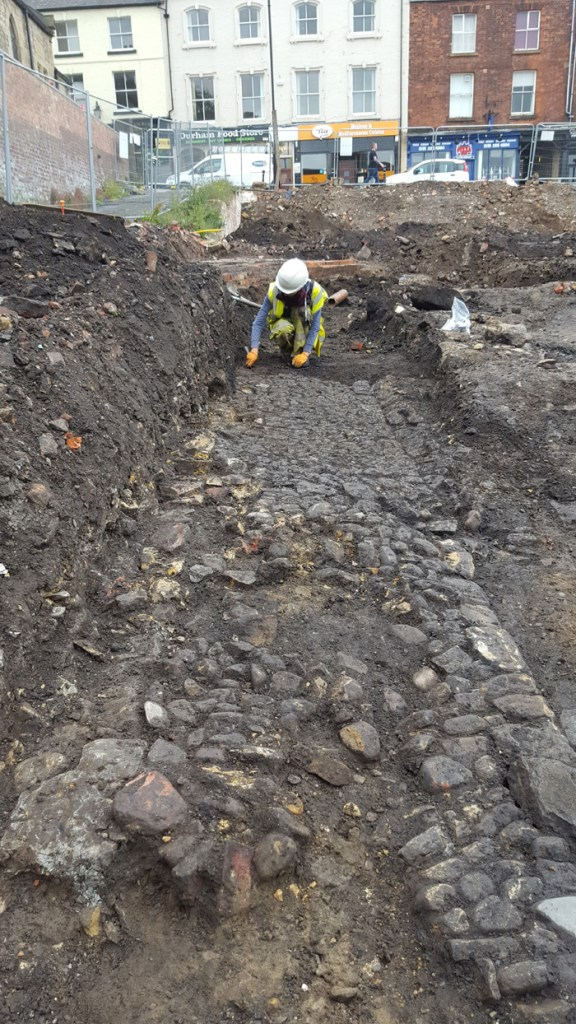 Archaeologists excavating a cobbled surface