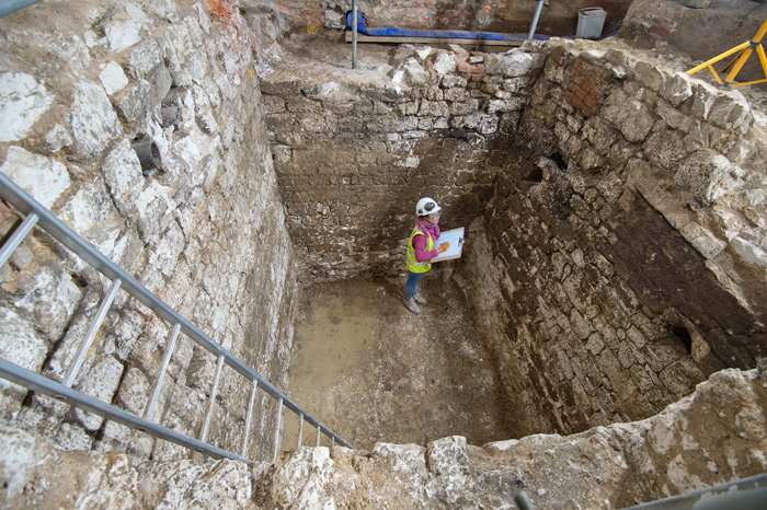 An archaeologist standing in a deep, brick-lined, square cesspit