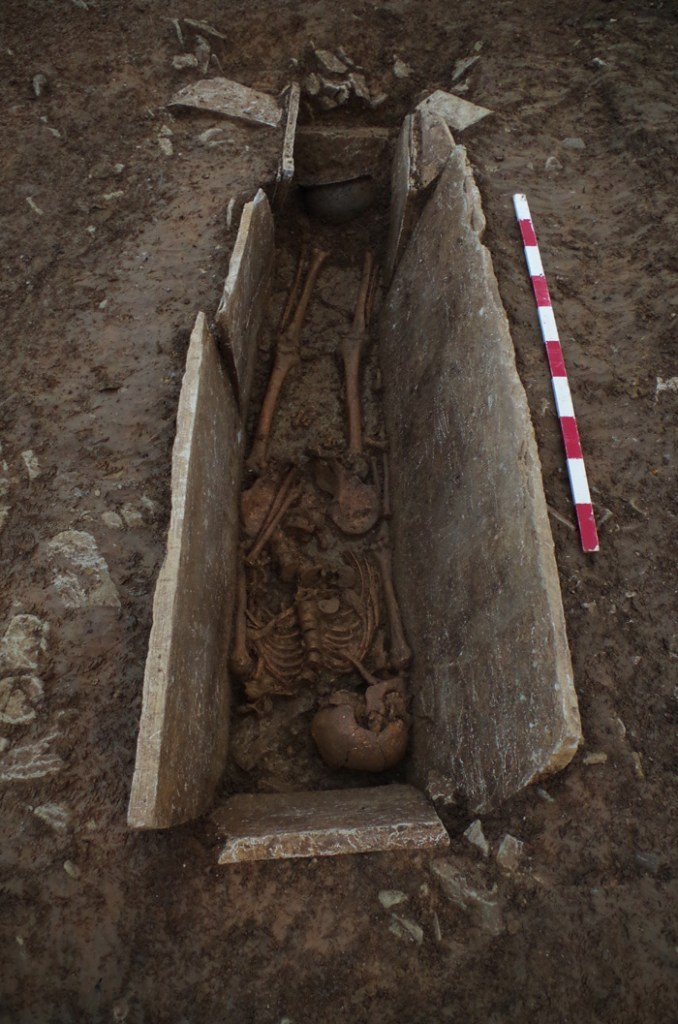 A skeleton in a stone cist burial with a cooking pot at its feet