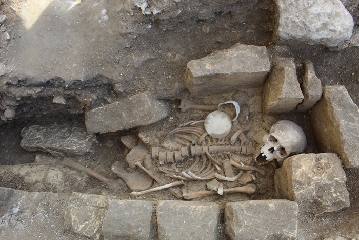 Stone-lined grave with skeleton and grave goods
