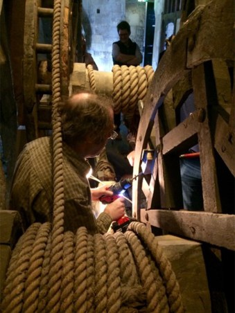 A man in the middle of the windlass mechanism taking a sample