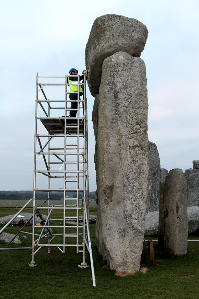 A photograh of a sarsen at Stonehenge with a sample being taken
