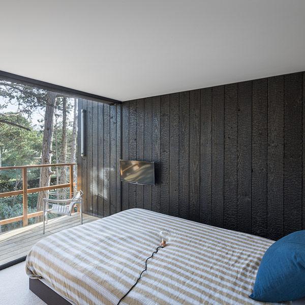 chambre des parents dans maison bois avec grandes fenêtres