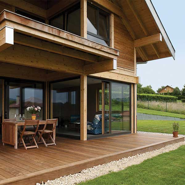 terrasse en bois bien traitée d'une maison bois avec jardin