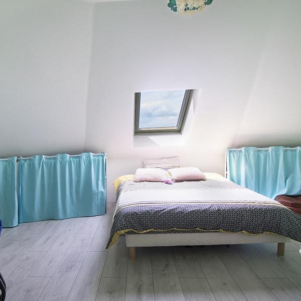 chambre des parents avec fenêtre dans une petite maison en bois