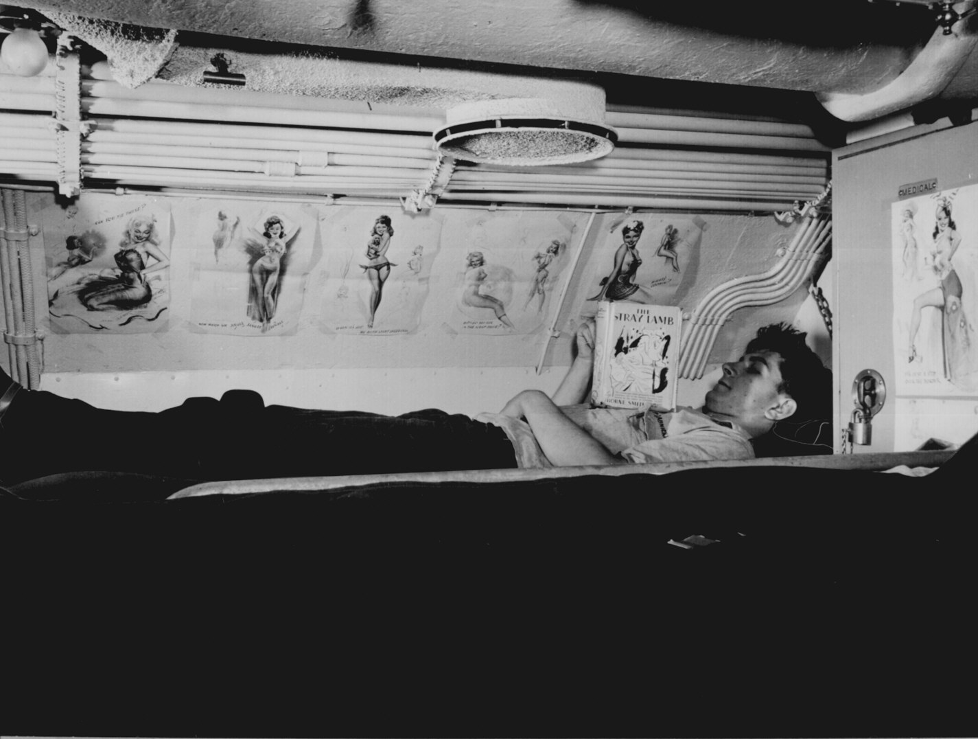 hight resolution of sailor reading in his bunk aboard uss capelin at submarine