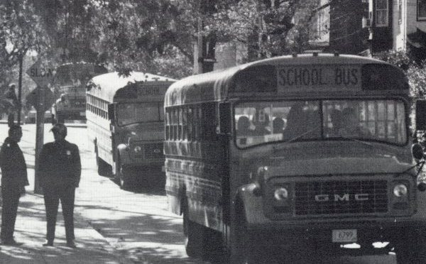 Officers from the Boston Police Department standing beside school buses. Photo from the 1975 Hyde Park High School yearbook.