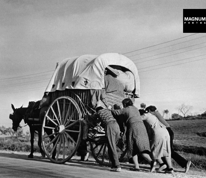 Civiles empujan un carruaje que les llevará a Barcelona, 1939