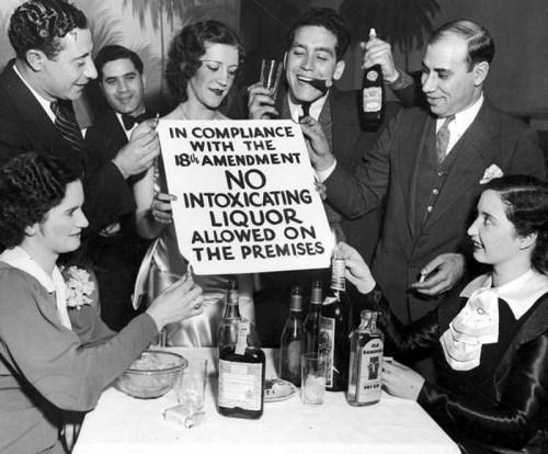 Grupo de hombres y mujeres posan con botellas de alcohol mientras sostienen un cartel prohibicionista, que declara la prohibición de bebidas alcohólicas en el establecimiento (s/f).
