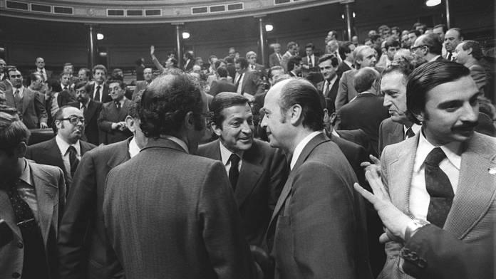 Adolfo Suárez, símbolo de la Transición española, rodeado por los parlamentarios de UCD tras la aprobación de la constitución. Fuente: El País (https://elpais.com/elpais/2018/08/29/opinion/1535554398_616477.html)
