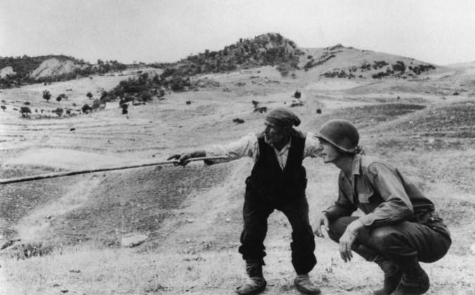 Un habitante de Sicilia da una serie de indicaciones a un soldado estadounidense. 1943. Robert Capa