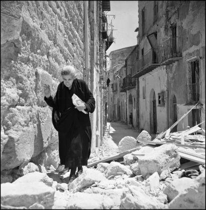 Una mujer de avanzada edad pasea por las ruinas de su pueblo. 1943. Robert Capa