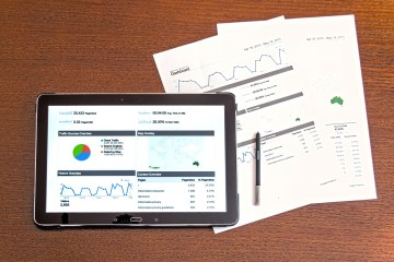 iPad and documents with graphs and charts