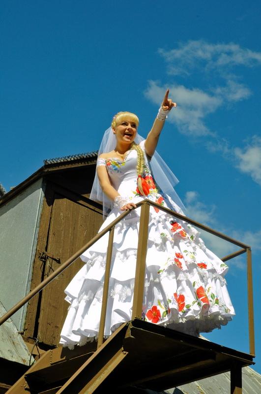 Нетерпеливая невеста, выглядывающая своего жениха с крыши дома. Жанровая свадебная фотография. Автор Сергей Рыжков