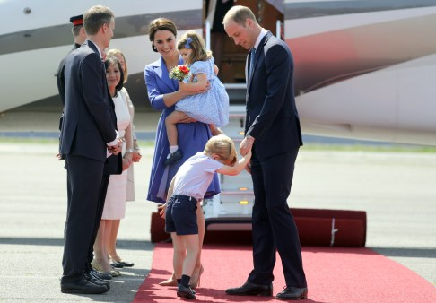Britain's Prince William, right, and his wife Kate, the Duchess of Cambridge with their children Prince George and Princess Charlotte at the airport in Berlin, Wednesday, July 19, 2017. The British royal couple is on a three-day-visit in Germany. (Steffi Loos/Pool Photo via AP)