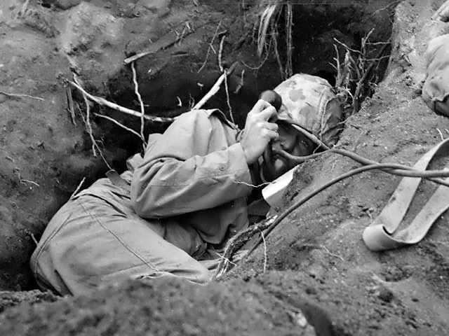 Burrowed in his shallow foxhole at the edge of Motoyama airstrip on Iwo Jima, a Marine communicator calls for artillery support to silence the enemy mortars that are pinning down the leatherneck advance.