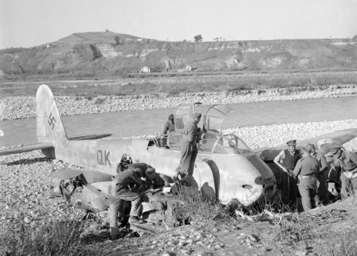 Men of the RAF Regiment assist an RAF intelligence officer to salvage important parts from a Messerschmitt Me 410 photographic reconnaissance aircraft, shot down on the banks of the Sangro River, Italy. The Me 410 A-3 from 2(F)./122 (Wk.Nr. 10253, F6+QK) was shot down by fighters and belly landed in the Sangro River while on a recconnaisance mission over the front lines in the Foggia-Bari-Termoli area on 26 November 1943. The crew, Ofw. Arthur Kammberger and Uffz. Vitus Mirlbach was captured.