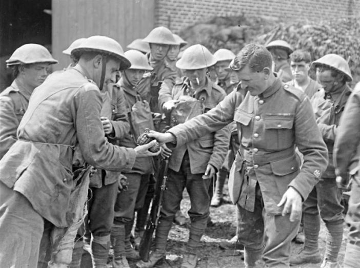RSM of the 11th Royal Scots serving out Mills bombs to a raiding party, July 1918.