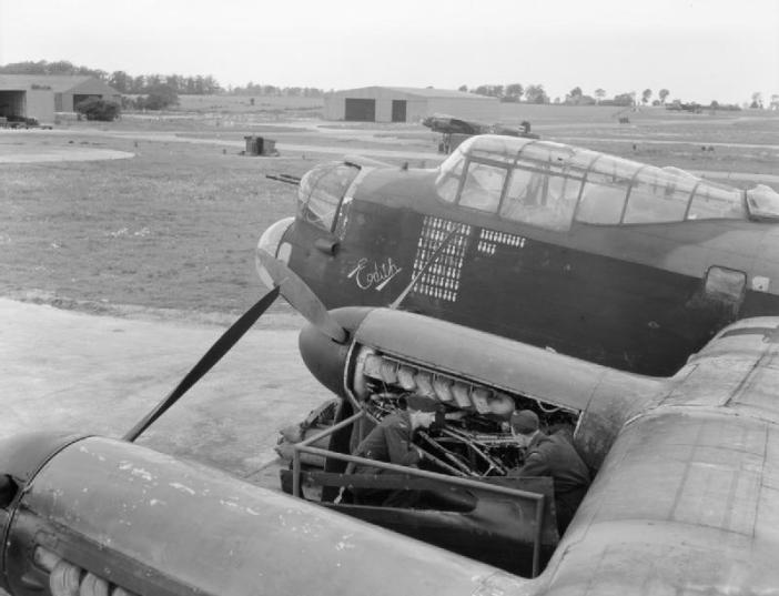 "Mechanics at work on an engine of Avro Lancaster B Mark III, LM577 'HA-Q' ""Edith"", of No. 218 Squadron RAF on a pan hardstanding at Chedburgh, Suffolk."