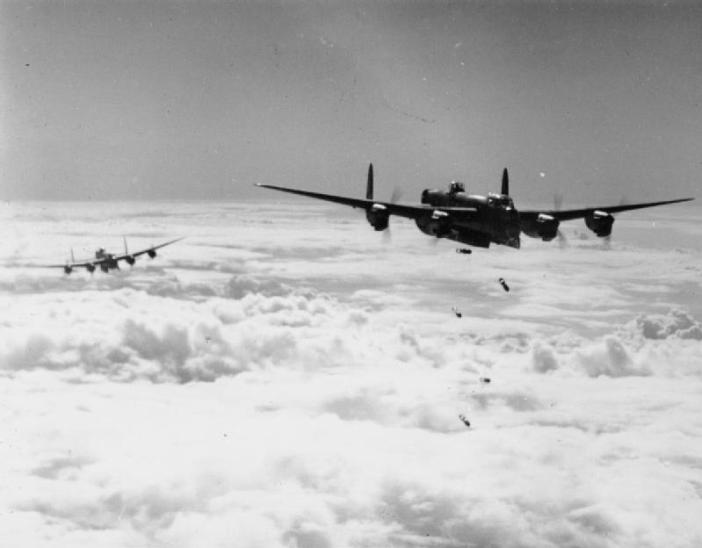 "An Avro Lancaster B Mark I or III of No. 514 Squadron RAF based at Waterbeach, Cambridgeshire, releases its bombs through cloud, during a daylight attack on a flying-bomb launch site at Les Catelliers in northern France, (""Noball"" Operation)."