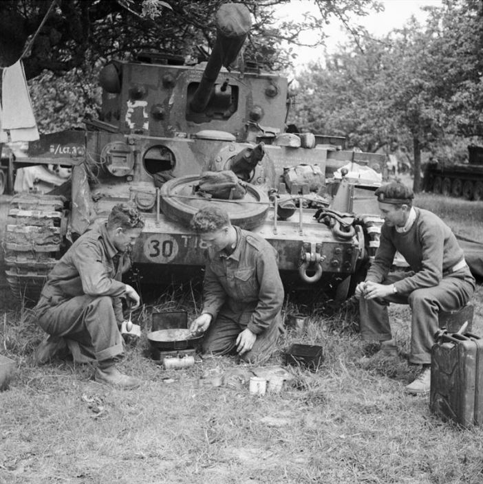 A Cromwell tank crew of 4th County of London Yeomanry, 7th Armoured Division, preparing a meal in front of their vehicle, 17 June 1944.