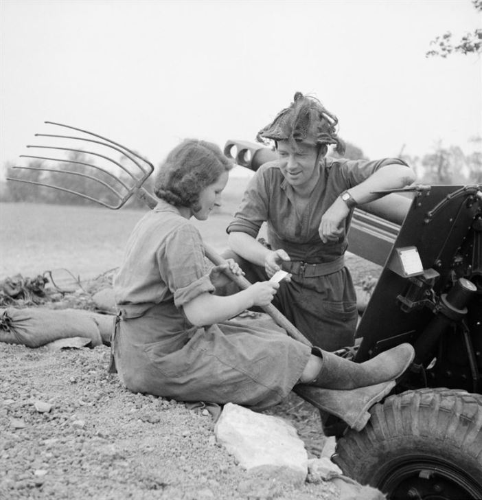 A gunner at a 25-pdr battery chats to a local French girl in Normandy, 20 July 1944.